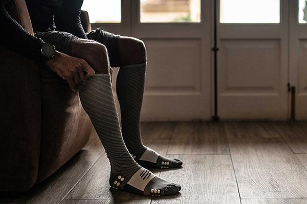 personne dans son canapé mettant les chaussettes full socks recorvery